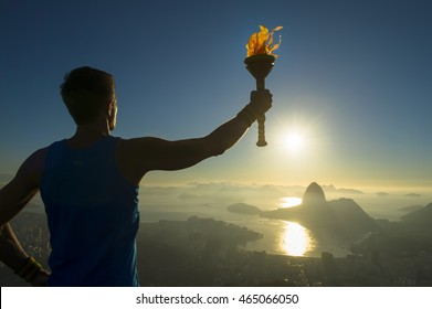 RIO DE JANEIRO - MARCH 05, 2015: Torchbearer athlete stands in silhouette holding a torch above a skyline of Sugarloaf Mountain and Guanabara Bay in celebration of the city hosting the Summer Games.