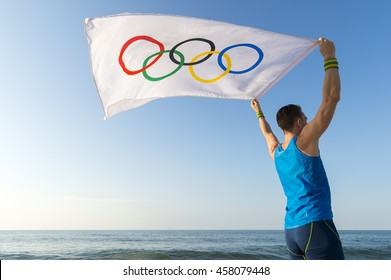 RIO DE JANEIRO - MARCH 10, 2016: Athlete holds Olympic flag at sunrise view over the calm sea in celebration of the Summer Games.