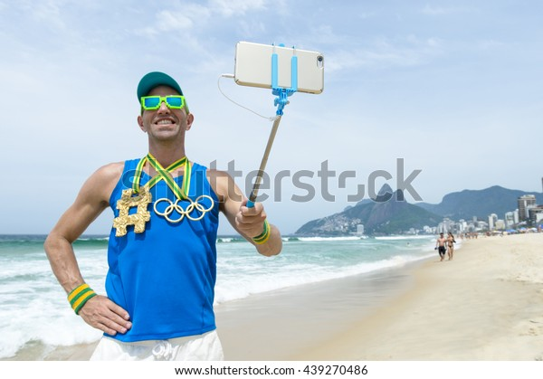 RIO DE JANEIRO - MARCH 10, 2016: Athlete with hashtag and Olympic rings gold medals stands taking a selfie on Ipanema Beach in celebration of the Summer Games.