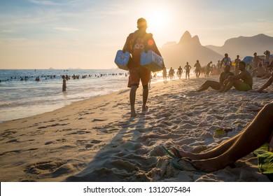 RIO DE JANEIRO - MARCH 15, 2015: A Brazilian beach vendor selling chilled mate, a type of South American tea, walks in orange uniform along the shore of Ipanema Beach.