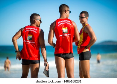 RIO DE JANEIRO - MARCH 15, 2018: A trio of Brazilian lifeguards in uniforms sponsored by the embattled oil company Petrobras monitor heavy surf on Ipanema beach.