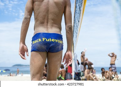 RIO DE JANEIRO - MARCH 17, 2016: A young Brazilian man wears swimwear branded with his team of futevolei (footvolley), a sport that combines football and volleyball, on the beach in Leblon.