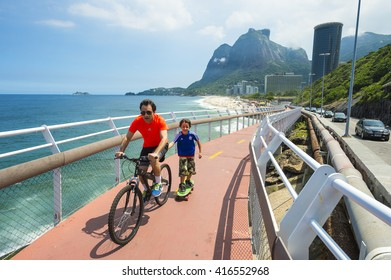 RIO DE JANEIRO - MARCH 19, 2016: A father and son ride along the newly completed Tim Maia bike path connecting Ipanema and Copacabana with Barra, a legacy project from the 2016 Olympic Games.