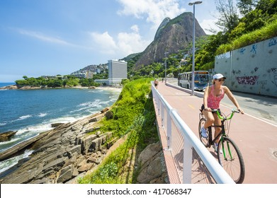 RIO DE JANEIRO - MARCH 19, 2016: A female cyclist rides along the newly completed Tim Maia bike path connecting Ipanema and Copacabana with Barra, a legacy project from the 2016 Olympic Games.