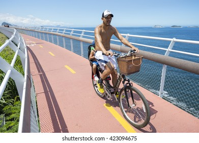 RIO DE JANEIRO - MARCH 19, 2016: Brazilian father and child ride a bicycle along the Ciclovia Tim Maia bike path, a legacy project of the 2016 Olympic Games connecting Ipanema and Copacabana and Barra