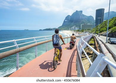 RIO DE JANEIRO - MARCH 19, 2016: Cyclist and scooter share the newly completed Ciclovia Tim Maia bike path, a legacy project from the 2016 Olympic Games connecting Ipanema and Copacabana with Barra.