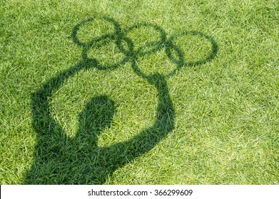 RIO DE JANEIRO - MARCH 20, 2015: Shadow of a man holds Olympic rings on a green grass playing field.