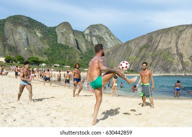 RIO DE JANEIRO - MARCH 20, 2017: Young Brazilians play a game of keepy-uppies (known locally as altinho) on the shore of Itacoatiara Beach.