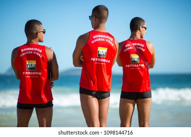 RIO DE JANEIRO - MARCH, 2018: A group of three Brazilian lifeguards stand in uniforms sponsored by the embattled state oil company Petrobras monitoring swimming conditions on Ipanema beach.