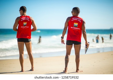 RIO DE JANEIRO - MARCH, 2018: A pair of athletic lifeguards in uniform (translation of Bombeiros Guarda Vidas: Firemen Lifeguards) monitor swimmers in the heavy surf on Ipanema Beach.