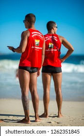 RIO DE JANEIRO - MARCH, 2018: A pair of athletic lifeguards in uniform monitor swimmers in the heavy surf on Ipanema Beach.