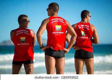 RIO DE JANEIRO - MARCH, 2018: A trio of Brazilian lifeguards in uniforms sponsored by the embattled oil company Petrobras monitor heavy surf on Ipanema Beach.