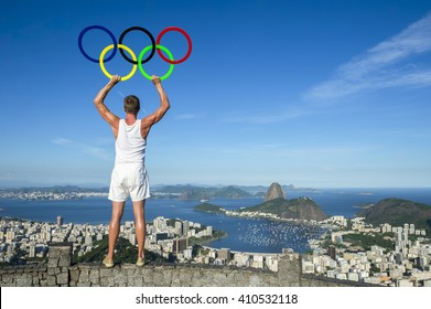 RIO DE JANEIRO - MARCH 21, 2016: An athlete holds Olympic rings under bright blue sky above the city skyline in anticipation of the city hosting the Summer Games.