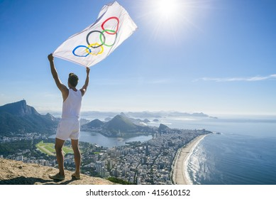 RIO DE JANEIRO - MARCH 21, 2016: Athlete stands holding Olympic flag above a city skyline view of Corcovado Mountain.