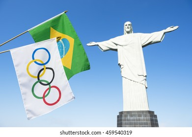 RIO DE JANEIRO - MARCH 21, 2016: Olympic and Brazilian flags hang next to the statue of Christ the Redeemer in celebration of the city hosting the Summer Games.
