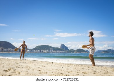 "RIO DE JANEIRO - MARCH 21, 2017: Brazilians play paddle ball (known locally as ""frescobol"") on Copacabana beach with Sugar Loaf mountain in the background."