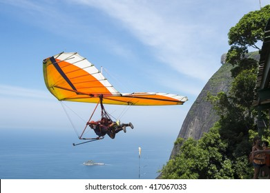 RIO DE JANEIRO - MARCH 22, 2016: A hang glider instructor takes off with a passenger from Pedra Bonita, in the Tijuca National Forest, heading toward the beach at Sao Conrado.