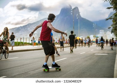 RIO DE JANEIRO - MARCH 24, 2017: A young Brazilian man passes on his skateboard on the Ipanema beachfront street, a car-free mecca for fitness and recreation on Sundays and holidays.