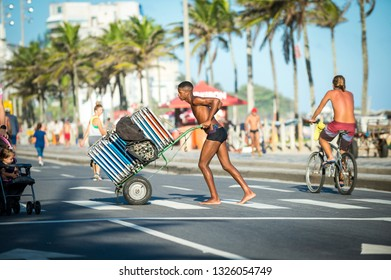 RIO DE JANEIRO - MARCH 26, 2017: A young Brazilian worker pushes a cart of folded chairs from a beach stand across the beachfront road in Ipanema.