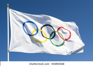 RIO DE JANEIRO - MARCH 27, 2016: An Olympic flag flutters in the wind against bright blue sky in celebration of the city hosting the Summer Games.
