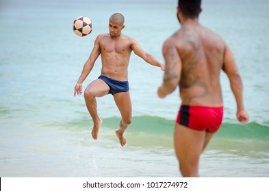 RIO DE JANEIRO - MARCH 4, 2017: A pair of young Brazilian men play a game of kick-ups football on the shore of Itacoatiara Beach.