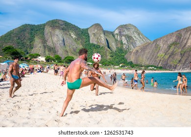 RIO DE JANEIRO - MARCH 4, 2017: A group of young Brazilian men play a game of keepy-uppies (known locally as altinho) on the shore of Itacoatiara Beach.