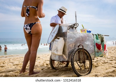 RIO DE JANEIRO - MARCH 6, 2016: A tourist on Ipanema Beach orders boiled corn from a vendor who travels Ipanema Beach with a custom cart full of boiling water.