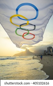 RIO DE JANEIRO - OCTOBER 27, 2015: An Olympic flag flutters in the wind in front of the sunset skyline on Ipanema Beach.