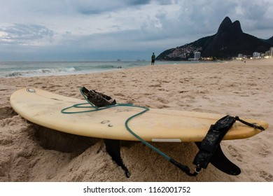 Rio de Janeiro, RJ / Brazil - 02 22 2016:  Surfboard lays at Ipanema beach (Praia de Ipanema) and Two Brothers hill (Morro Dois Irmaos) is in the background.