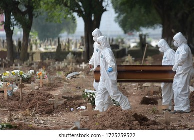 RIO DE JANEIRO,(BRAZIL),APRIL,06,2020: funeral of victim of the covid-19, new coronavirus, in the cashew cemetery in rio de janeiro with the gravediggers wearing clothes against contamination