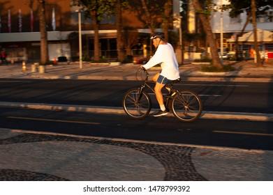 Rio de Janeiro-RJ-Brasil-07-31-2019-Horizontal panning photograph of man in white shirt, shorts, helmet using bicycle on cycling track.Beach Copacabana Beach.Isolated.