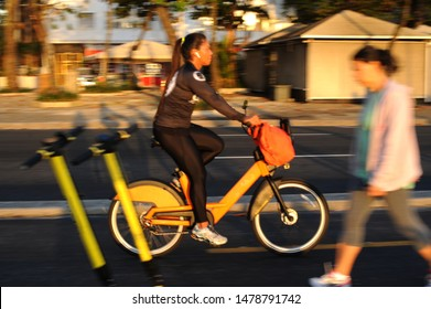 Rio de Janeiro-RJ-Brasil-07-31-2019-Panning photo.First shot defocused electric scooter, stationary.Cyclist with electric bike strolling and pedestrian walking.Copacabana beach.