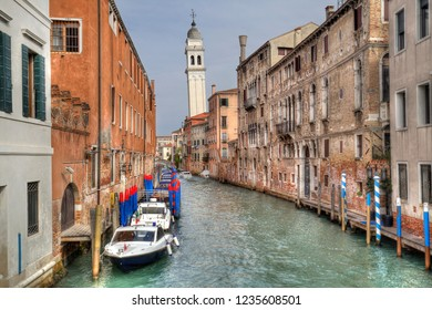 Rio del Greci canal with colorful bollards, small boats and the tower of the Greek Orthodox church in Venice, Italy