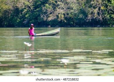 RIO DULCE, GUATEMALA - MARCH 10, 2016: Local indigenous woman paddling across Rio Dulce river, Guatemala