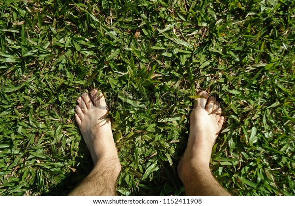 Teutônia, Rio Grande Do Sul/Brazil - July 29, 2018: A barefoot person relaxes stepping on the grass.