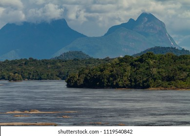 'Rio Negro' river rapids. Blue sky with clouds. Mountains and rainforest in the background. Sunny day, telephoto lens shot. São Gabriel da Cachoeira, Amazonas / Brazil