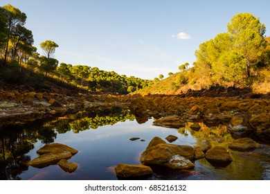 Rio Tinto in Huelva district, Andalusia, Spain. Amazing color of the rocks and water. Red river. Beautiful landscape before sunset with  reflections and symmetry. iron in the water.