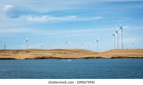 RIO VISTA, CA/U.S.A. - OCTOBER 6, 2016: A photo of the Sacramento River with powerboat flowing in the San Joaquin Delta with the Montezuma Hills wind turbine project in the background.