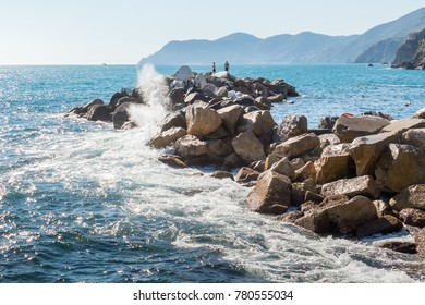 Riomaggiore, Cinque Terre, Italy, July 3, 2017: Waves break against a rocky breakwater as two men stand on the rocks looking out to sea.