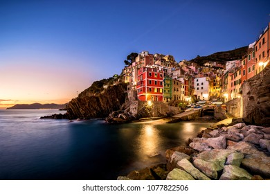 Riomaggiore fisherman village at sunset. Riomaggiore is one of five famous colorful villages of Cinque Terre in Italy, suspended between sea and land on sheer cliffs. Liguria, Italy