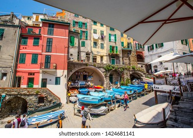RIOMAGGIORE, ITALY - June 2019: Beautiful view of the small fishing boats and traditional houses in Riomaggiore village in Cinque Terre National Park, Riomaggiore, Liguria, Italy