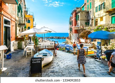 Riomaggiore, Italy - September 18 2018: Tourists enjoy a sunny day on the Ligurian coast with the sea, cafe and boats in Riomaggiore Italy, on the Cinque Terre of the Italian Riviera