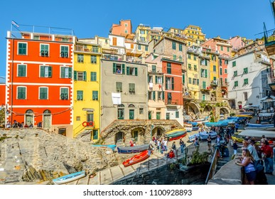 Riomaggiore, Italy - September 25 2017: Tourists and locals enjoy an autumn afternoon at the boat launch of the colorful village of Riomaggiore Italy, part of the Cinque Terre