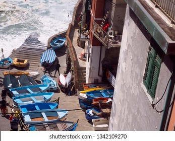 RIOMAGGIORE, ITALY-SEPTEMBER:  Small commercial boats are seen lined up on pavement with tourists in Riomaggiore, Cinque Terre, Italy in September 2018.