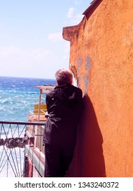 RIOMAGGIORE, ITALY-SEPTEMBER: An unidentified man is seen  looking at sea by old waterfront building in seaside Riomaggiore, Cinque Terre, Italy  in September 2018.