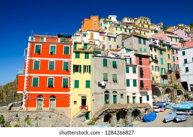 Riomaggiore traditional typical Italian fishing village in National park Cinque Terre with colorful multicolored buildings houses close-up on hill and boats, clear blue sky background, Liguria, Italy