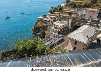 Riomaggiore train station from above with train approaching, platform full with tourist and boats on the blue sea in the background