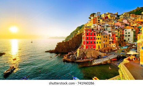 Riomaggiore village along the coastline of Cinque Terre area at sunset in Italy.