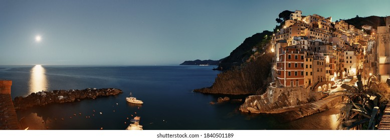 Riomaggiore waterfront view with buildings and moonset in Cinque Terre at night panorama, Italy.