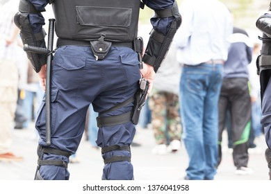 Riot police officer holding hand on his gun during street protest